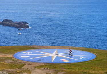 SPA8823AW Spain, Galicia, La Coruna, Large compass in front of the Hercules tower, cyclist crossing compass