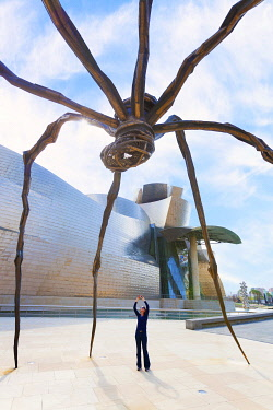 SPA8755AW Spain, Bilbao, Guggenheim museum with Maman, by Louise Bourgeois, 30-foot-tall spider, woman photographing (MR)