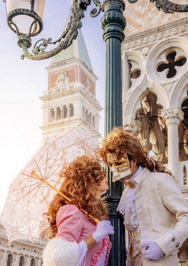 ITA13775AW Venice, Veneto, Italy; Two masked lovers in the city during Carnival, St. Mark's Tower in background