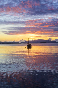 IBXHAN04812633 Sunset over the sea and wooden boat, Crinan, Scotland, Great Britain