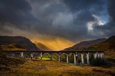 IBXSEI04810426 Glenfinnan railway viaduct, with autumn colours and dramatic cloudy skies, Glenfinnan, West Highlands, Scotland, Great Britain