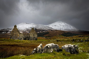 IBXSEI04810772 Rocks with white caps and house ruin in Highland landscape with snowy Cullin mountains in the background, Broadford, Isle of Skye, Scotland, United Kingdom, Europe