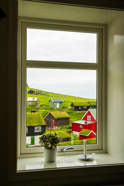 CLKRM97478 Iconic houses with grass roof seen through a window, Mykines island, Faroe Islands, Denmark