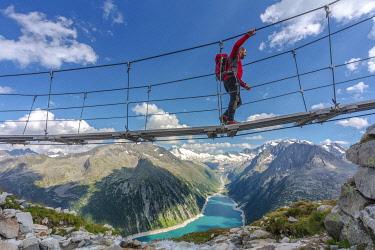 CLKMG95181 Hiker on the tibetan bridge near Olperer hut with Schlegeispeicher lake on the background, Zillertal Alps, Tyrol, Schwaz district, Austria (MR)