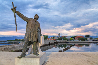 CLKMG98672 monument of Branimir of Croatia in Nin, on the background the old bridge that connects the old town to the mainland, Nin, Zadar county, Dalmatia, Croatia