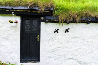 CLKRM97459 Flowerpot and ornaments on facade of iconic house with grass roof, Mykines island, Faroe Islands, Denmark