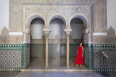 CLKDC99161 A woman in a typical arabic horseshoe arch in Palacio de Pedro I (Palace of Peter I), Royal Alcazars of Seville, Seville, province of Seville, Andalusia, Spain (MR)