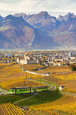 CLKMC99354 View of the medieval Aigle castle and the surrounding vineyards and railway in autumn. Canton of Vaud, Switzerland.