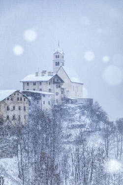 CLKMG105116 the ancient village of Colle Santa Lucia with the church on the hill under a snowfall, agordino, Belluno,Veneto, Italy