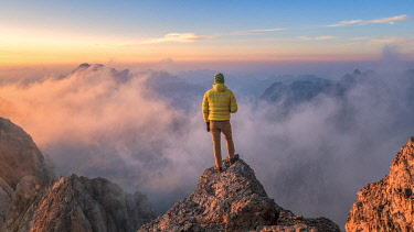 CLKMG95196 mountaineer admires the landscape at sunrise from a rock spur near Punta Penia, Marmolada, Belluno and Trento, Dolomites, Italy (MR)