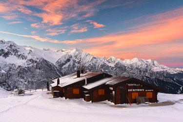 CLKMR99117 Nigritella refuge in Winter season at dawn, Stelvio national park in Camonica valley, Lombardy district, Brescia province, Italy.