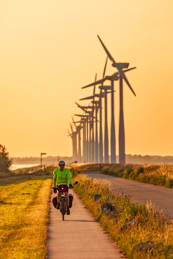 Caucasian male cyclist, cycling on a dijk cycleway adjacent to modern electricity generating windmills at sunset, overlooking the Eemmeer Lake on the Eemmeerdijk, Eemhof, The Netherlands.