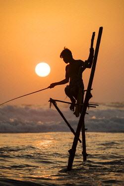 SRI2267AW Stilt Fishermen at dusk, Weligama, South Coast, Sri Lanka, Asia
