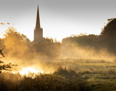 ENG16159 Mist rising above the River Windrush at sunrise, with the church at Burford in the background, Oxfordshire Cotswolds, England