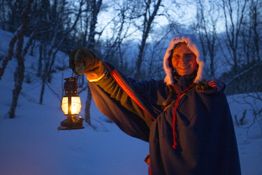 Sami storyteller at Malangen Resort near Tromso in northern Norway, walking through winter woodland with an oil lamp