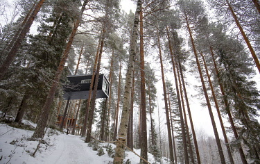 The Cabin (designed by architects Cyren & Cyren) suspended in pine trees at the Treehotel near Lulea, Lapland, Sweden.