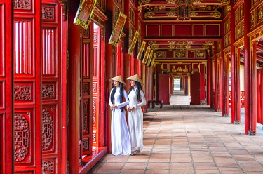 VIT1551AW Two young women wearing traditional national costume, ao dai, in the Imperial City, Hue, Vietnam