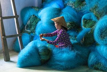 VIT1563AW A Vietnamese woman mending blue fishing net, Mekong Delta, Vietnam