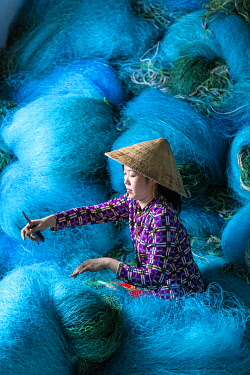 VIT1566AW A Vietnamese woman mending blue fishing net, Mekong Delta, Vietnam