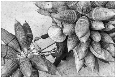 VIT1593AW A man on the bicycle loaded with the conical bamboo fish traps, near Hanoi, Vietnam