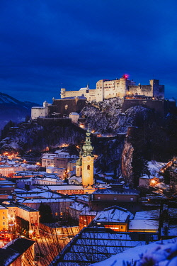 AUT0957AWRF Elevated view of Salzburg city by night on a winter evening with the roofs covered with snow and the Hohensalzburg Castle