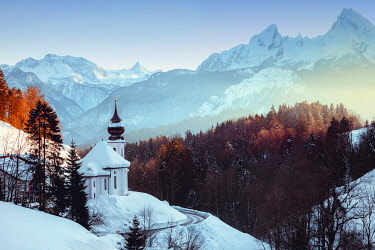 GER11731AW View of the church of Wallfahrtskirche Maria Gerna at sunset in winter sorrounded by snow with the Alps  un the background