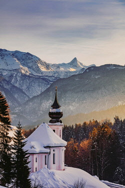 GER11732AW View of the church of Wallfahrtskirche Maria Gerna at sunset in winter sorrounded by snow with the Alps  un the background