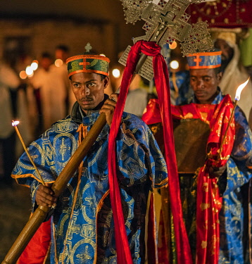 ETH3514 Ethiopia, Aksum, Tigray Region.  Church deacons of the Ethiopian Orthodox religion carry a heavy cross and bible at an early morning candlelight parade to celebrate the patron saint of St. Mary of Tsi...