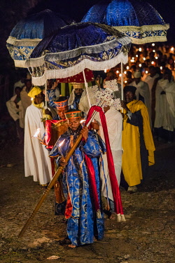 ETH3517 Ethiopia, Aksum, Tigray Region.  Church deacons of the Ethiopian Orthodox religion lead an early morning candlelight procession carrying a heavy cross and bible to celebrate the patron saint of St. Ma...