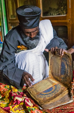 ETH3521 Ethiopia, Adwa, Tigray Region.  The Abbot of the Abba Garima monastery looks at one of the two New Testament gospels kept in the monastery. They are believed to be the oldest illustrated gospels in th...