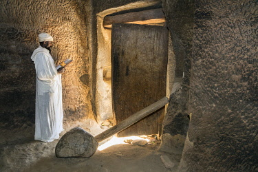 ETH3539 Ethiopia, Nebelet, Tigray Region.  A priest reads a prayer book by the light cast from a large wooden door in the rock-hewn church of Wukro Maryam. The top and bottom hinges of the door are rounded wo...