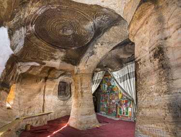 ETH3546 Ethiopia, Takatisfi, Tigray Region, Mikael Milhayzenghi church.  This small simple rock-hewn church was excavated from solid rock about the 8th century.  It features a beautifully carved low relief do...