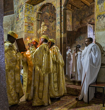 ETH3566 Ethiopia, Abraha Atsbeha, Tigray Region.  A deacon reads a passage from theBible by the light of a taper in the rock-hewn church of Abraha wa-Atsbeha during a midnight mass to celebrate Enkutatash, th...