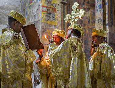 ETH3567 Ethiopia, Abraha Atsbeha, Tigray Region.  A deacon reads a passage from theBible by the light of a taper in the rock-hewn church of Abraha wa-Atsbeha during a midnight mass to celebrate Enkutatash, th...