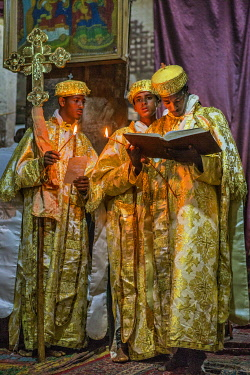ETH3568 Ethiopia, Abraha Atsbeha, Tigray Region.  A deacon reads a passage from the Bible by the light of a taper in the rock-hewn church of Abraha wa-Atsbeha during a midnight mass to celebrate Enkutatash, t...