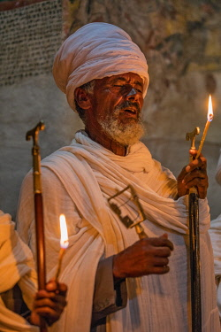 ETH3574 Ethiopia, Abraha Atsbeha, Tigray Region.  A Priest chants with sistra and prayer stick in the rock-hewn church of Abraha wa-Atsbeha during amidnight mass to celebrate Enkutatash, the Ethiopian NewYear...