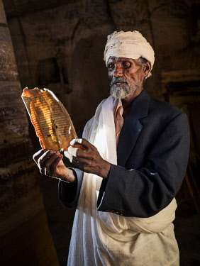 ETH3584 Ethiopia, Gheralta Mountains, Tigray Region.  A Priest in the ancient rock hewn church of Abuna Gebre Mikael reads an old manuscript with the help of sunlight streaming through the only window in the...