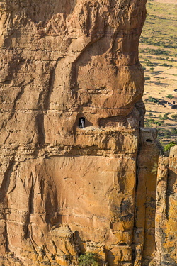 ETH3586 Ethiopia, Gheralta Mountains, Tigray Region.  A priest stands outside the entrance to the rock-hewn church of Abuna Yemata, which was carved into a sandstone pillar around the sixth century.  The clim...