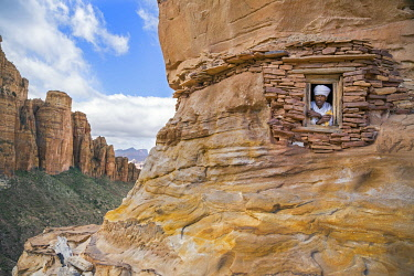 ETH3590 Ethiopia, Gheralta Mountains, Tigray Region.  A priest looks out of the only window in the rock-hewn church of Abuna Yemata which was carved into a sandstone pillar around the sixth century.  The view...