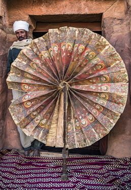 ETH3608 Ethiopia, Gheralta Mountains, Tigray Region.  An Ethiopian Orthodox priest displays a very rare fifteenth century ceremonial fan made of parchment at the entrance to the ancient rock-hewn church of Ab...