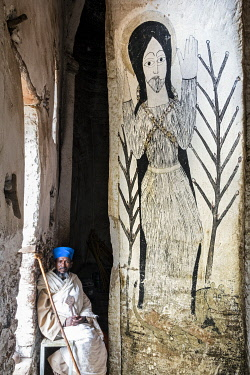 Ethiopia, Tembien, Tigray Region. A monks sits at the entrance to Abba Yohanni monastery which was carved into a sheer rockface at Debre Asa sometime after the thirteenth century. The mural is of Abb...