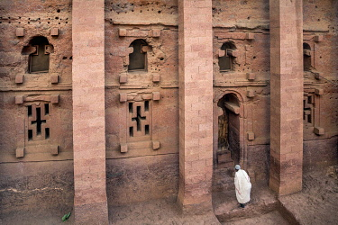 ETH3622 Ethiopia, Lalibela, Amhara Region. A worshipper prays at Bete Medhane Alem which is the largest ancient rock-hewn church in Lalibela.  This side view shows an upper row of wide steleform windows and a...