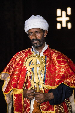 ETH3625 Ethiopia, Lalibela, Amhara Region. A priest in the ancient rock-hewn church of Bete Medhane Alem holds the seven-kilogram priceless Lalibela cross which is revered for its exceptional healing power.