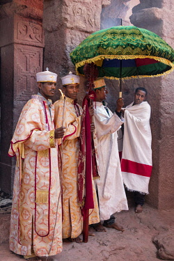 ETH3636 Ethiopia, Lalibela, Amhara Region. Deacons stand outside the ancient Ethiopian Orthodox rock-hewn church of Bete Maryam with a ceremonial cross beneath a brocade umbrella during a service.