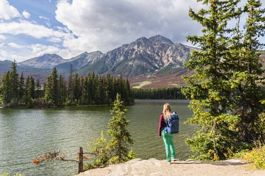 IBXMMW04833348 Female hiker stands on the lakeshore, Pyramid Lake, back mountains, Pyramid Mountain, Jasper National Park National Park, Canadian Rocky Mountains, Alberta, Canada, North America
