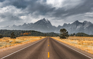 IBXMMW04848779 Highway in front of rugged mountains with cloudy skies, Grand Teton Range, Grand Teton National Park, Wyoming, USA, North America
