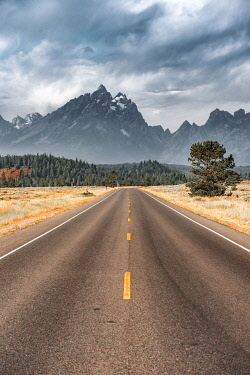 IBXMMW04848782 Highway in front of rugged mountains with cloudy skies, Grand Teton Range, Grand Teton National Park, Wyoming, USA, North America