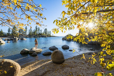 IBXMMW04850206 Young woman in bikini standing on a round stone in the water, bay at lake Lake Tahoe, Sand Harbor State Park, shore, California, USA, North America