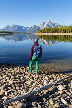 IBXMMW04850453 Young woman with rucksack standing on shore, mountains reflected in lake, Colter Bay, Jackson Lake, Teton Range, Grand Teton National Park, Wyoming, USA, North America
