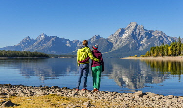 IBXMMW04850470 Young woman and young man standing side by side on the shore, looking into the landscape, mountains reflected in the lake, Colter Bay, Jackson Lake, Teton Range mountain range, Grand Teton National Pa...